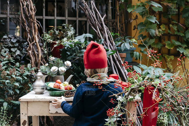 A girl sitting outside with a Christmas holly wreath