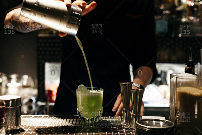A bartender pours a drink at a bar