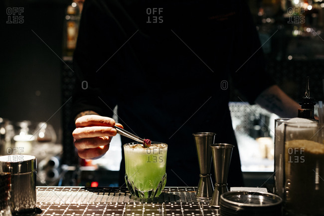 A bartender drops a rosebud in a drink at a bar