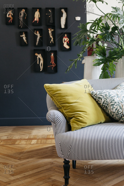 A striped couch on a parquet floor