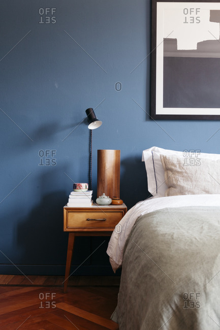 A bedroom with blue walls and a parquet floor