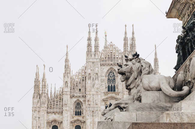 A stone lion in front of the Milan Cathedral