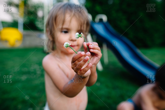 Girl in yard holding weed