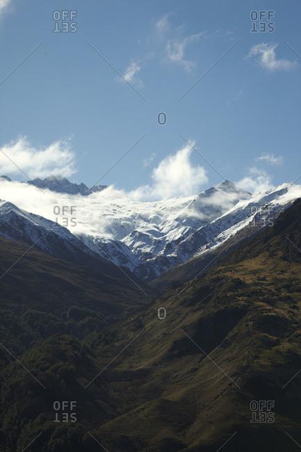 Verdant mountain range by snow capped peaks
