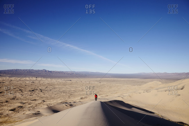 Person walking in remote sand dunes