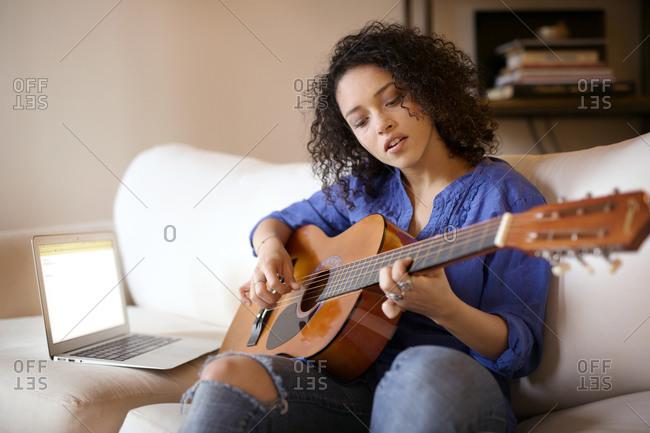 Woman playing guitar next to a laptop
