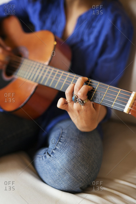 Close up of a woman playing acoustic guitar