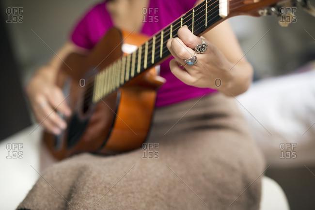 Woman strumming a guitar