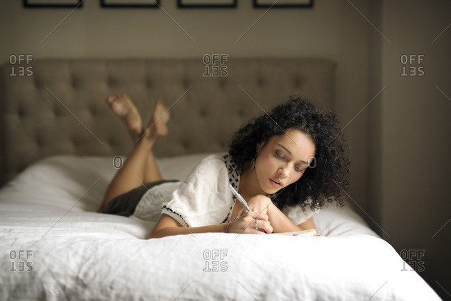 Woman writing in a journal on a bed