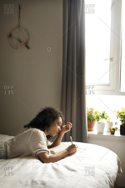 Woman lying on a bed writing in a journal