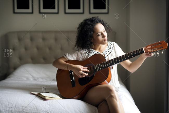 Woman at home playing guitar
