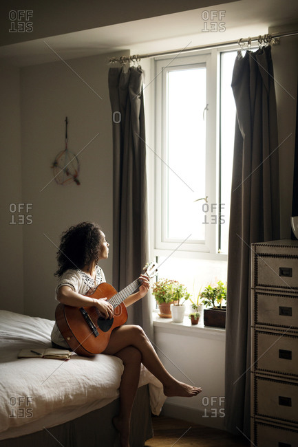 Woman playing guitar and looking out window