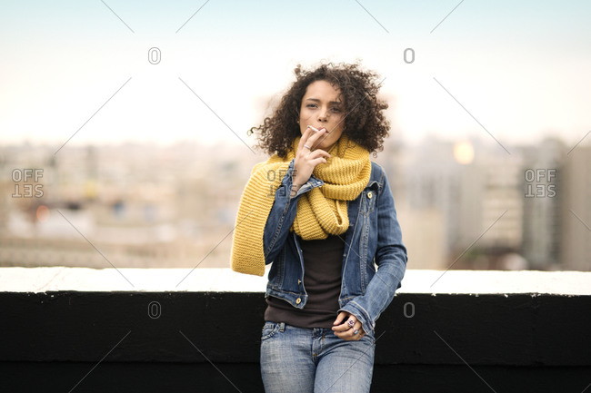 Young woman on a rooftop smoking