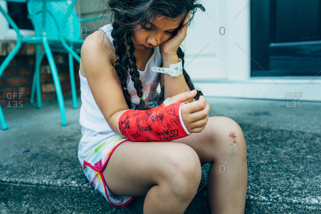 Sad girl with her arm in a cast