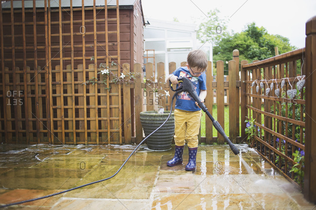 Little boy power washing a patio