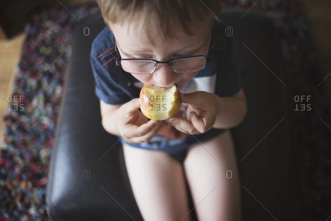 Little boy biting an apple