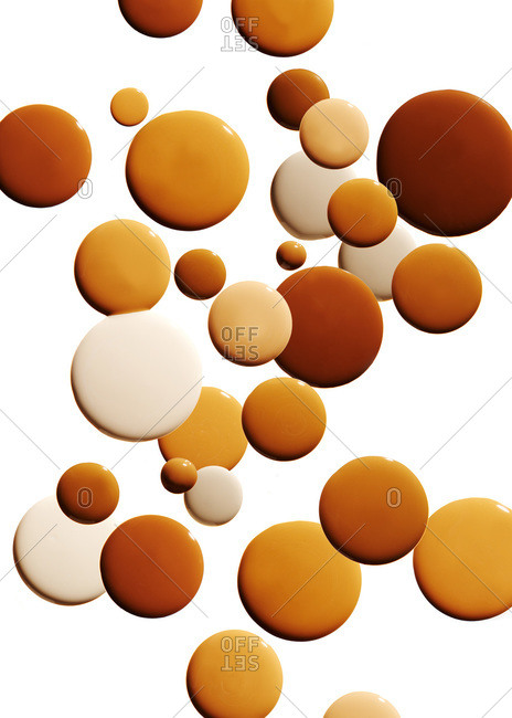 Various hues of foundation against a white background