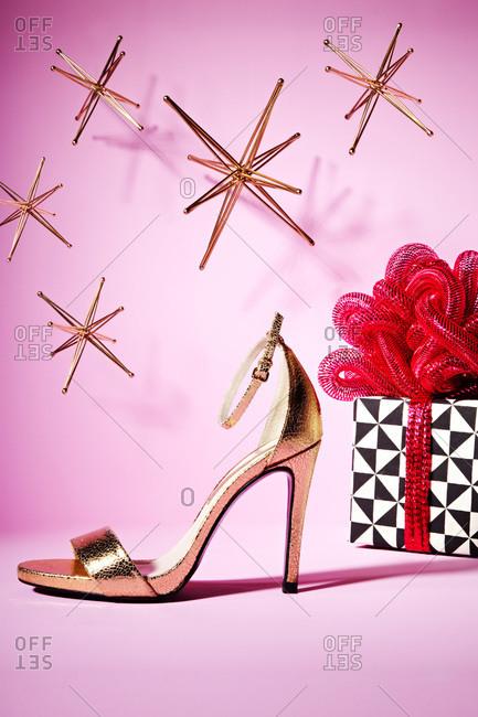 A high heel sandal next to a present
