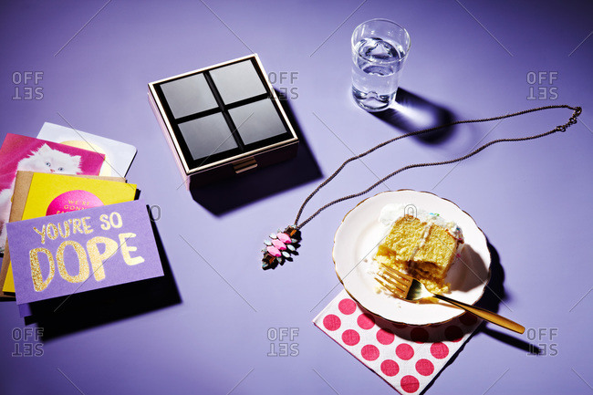 A slice of birthday cake with cards and jewelry