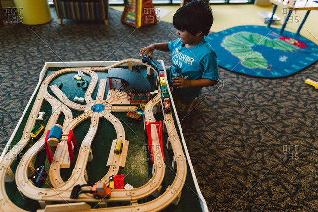 Boy playing with a wooden train set