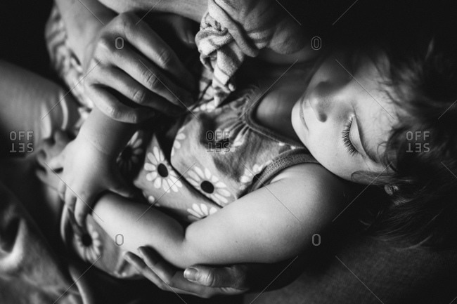 Close up of little girl sleeping in her parent's lap