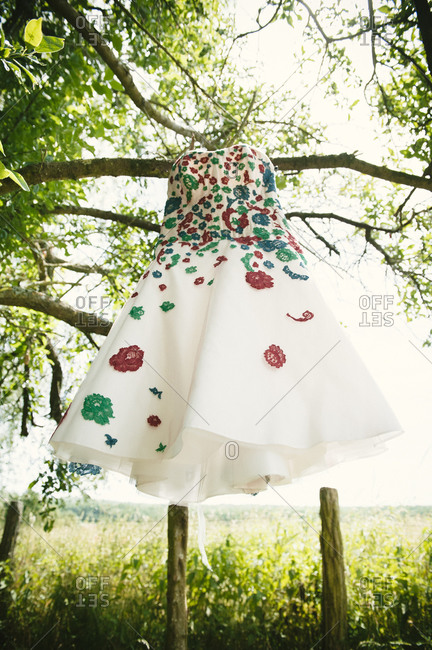 Floral wedding dress hanging from a tree branch