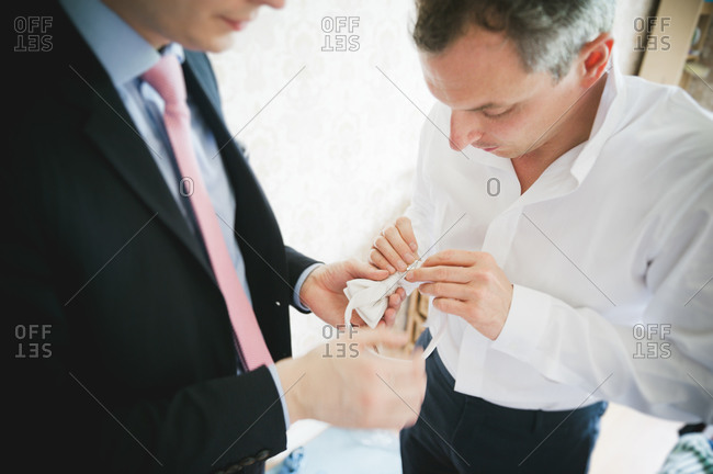 Groom and his best man trying to figure out a bow tie
