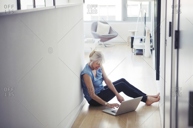 Woman using a laptop on the floor