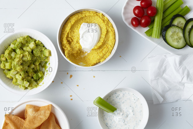 Three types of dips served with chips and vegetables