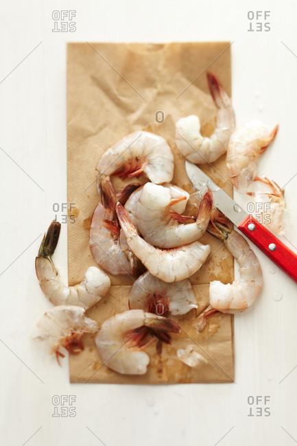 Raw shrimp on a paper bag with a shrimp knife