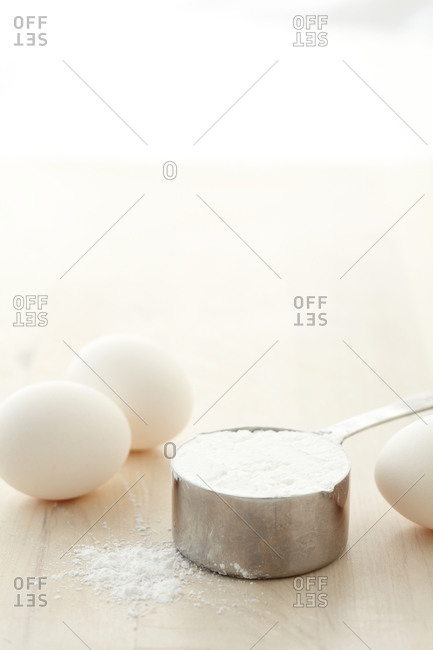 A cup of flour and white eggs