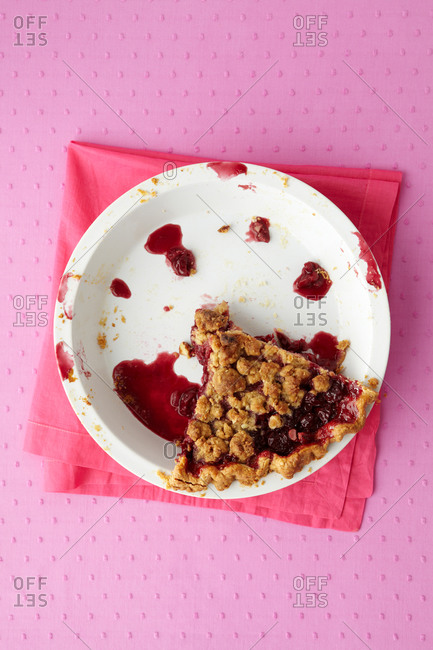 A few remaining slices of a glazed sweet cherry pie with almonds