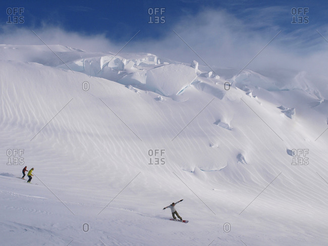 Mountaineers are skiing and snowboarding in the evening light, near 12000 feet camp on a glacier on Mount McKinley