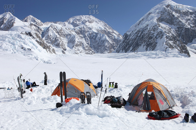 A team of mountaineers is resting in their camp with tents on the lower Kahiltna glacier on their way to Mount McKinley in Alaska