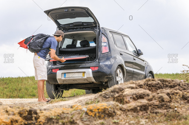 Male body boarder packing his car , after a surfing session in a spot near Areia Branca, Portugal.