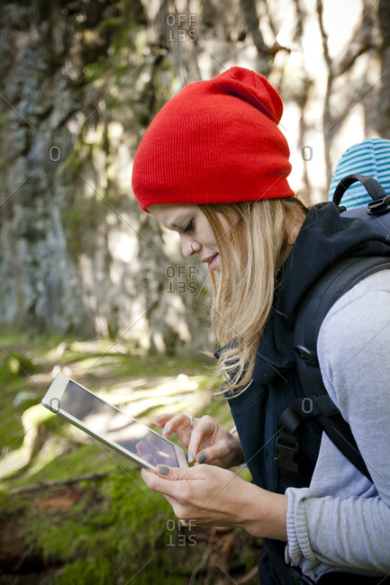 A young woman works on her tablet while walking through the forest