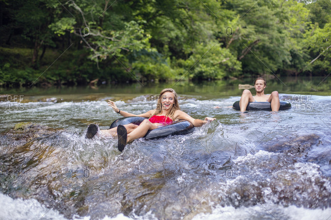 A young woman smiles while anticipating going over rapids in a tube on a river