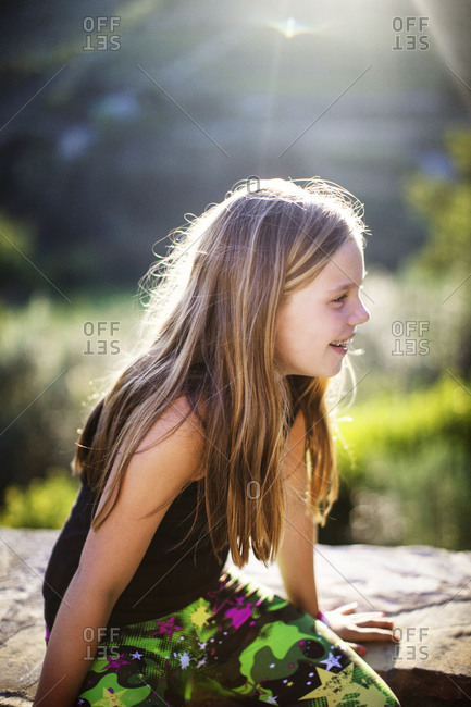 Young girl sitting on rock in sunlight