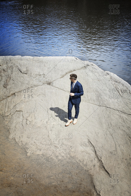 Man in suit on rock by water