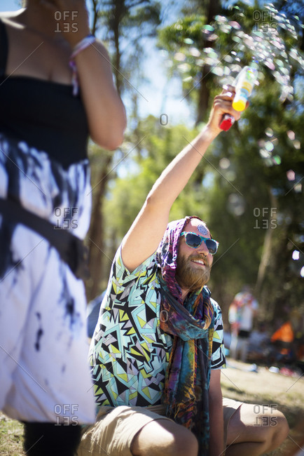 A man blows bubbles at an outdoor music festival