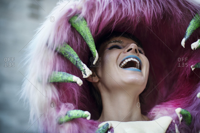 A woman in an outlandish furry hood laughs