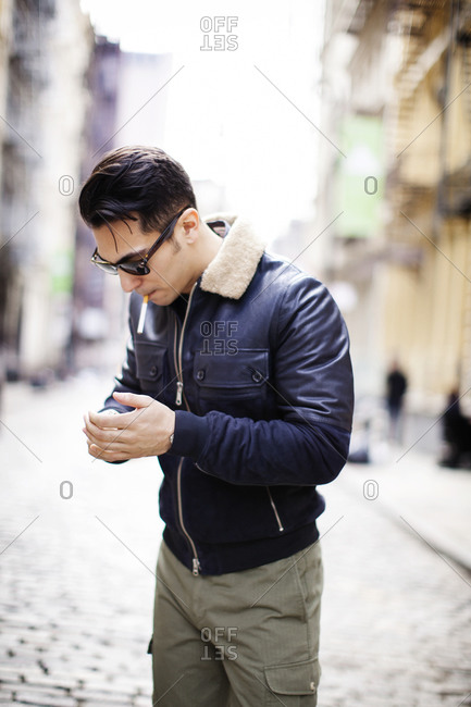 A young man in a leather coat lights a cigarette