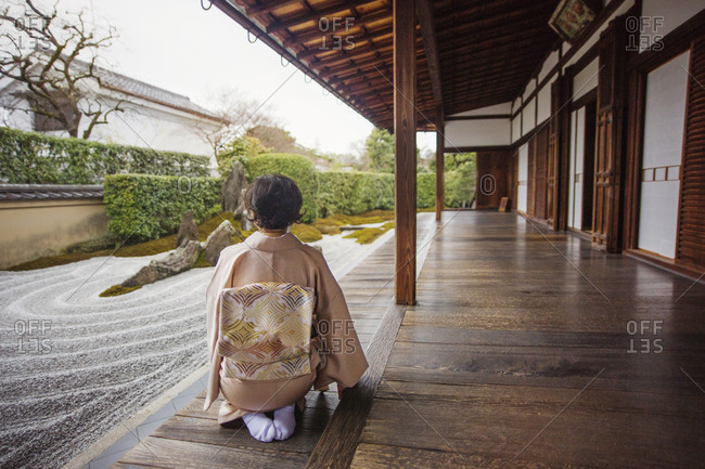 A woman admires a Japanese rock garden from her porch