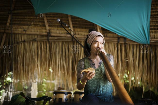A man plays a didgeridoo at a new age retreat