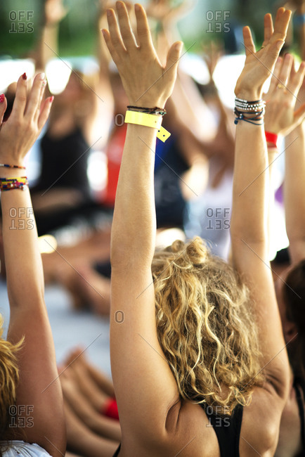 A woman raises up her hands at a new age retreat