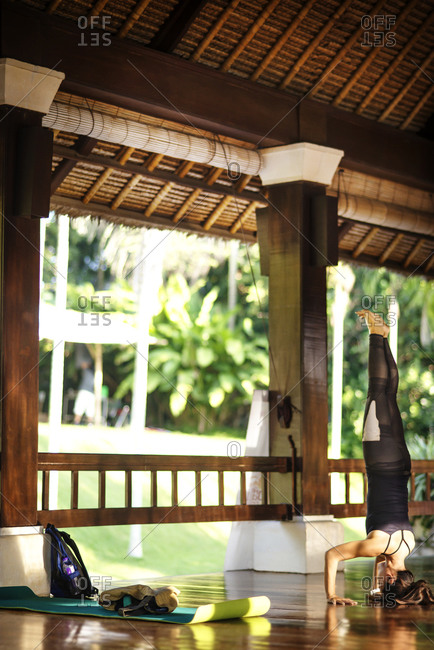 A woman does a headstand at a yoga retreat