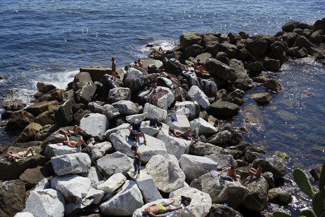 Liguria, Italy - May 31, 2015: Sunbathers on rocks in Levanto, in the Cinque Terre area of Liguria