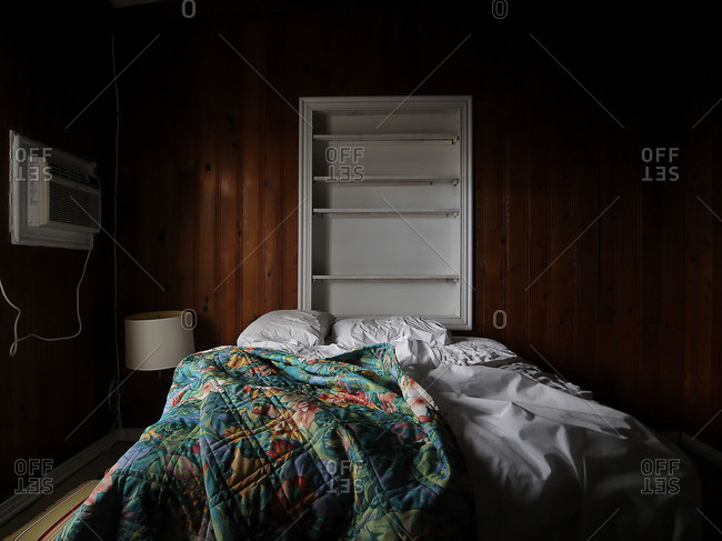 Unmade bed in a sparse room