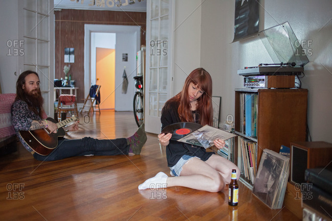 Woman looking at a record while her boyfriend plays guitar