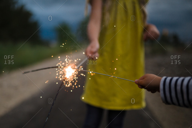 Kids lighting sparklers on remote road